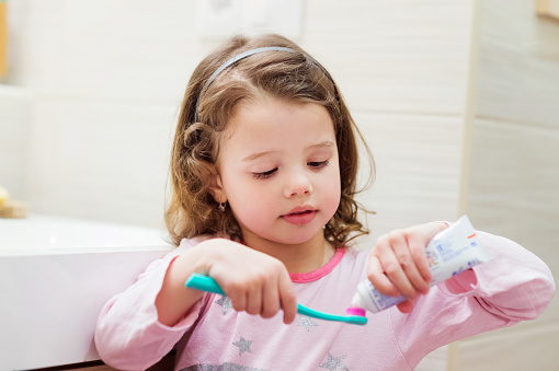 Young girl applying toothpaste to her toothbrush