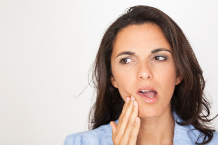 A woman suffering from tooth pain giving her a migraine.