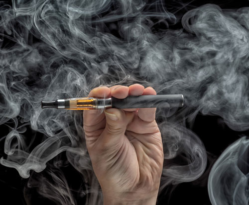 A man holding a vaping pen and blowing smoke.